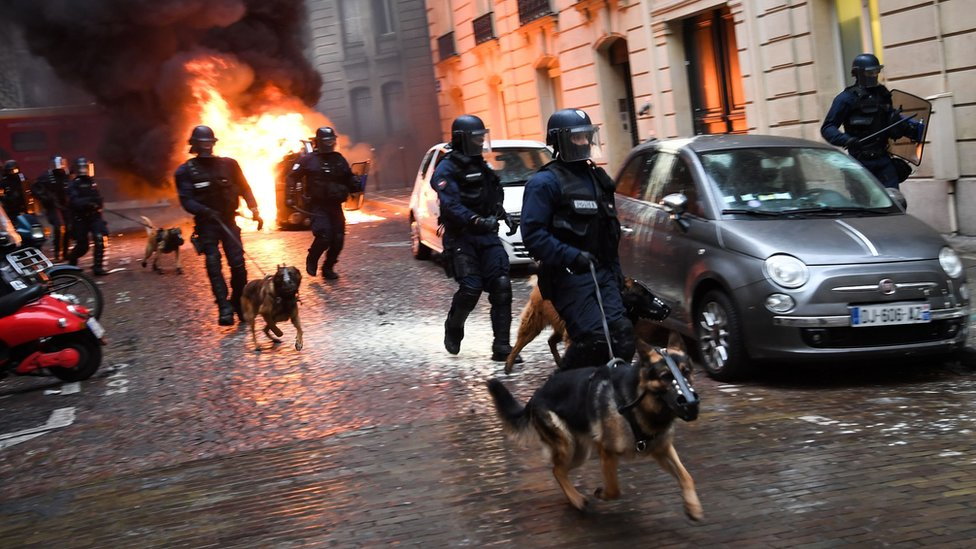 Riot police run next to a car set on fire during a protest of Yellow vest (Gilet Jaune) against rising costs of living they blame on high taxes on December 8, 2018