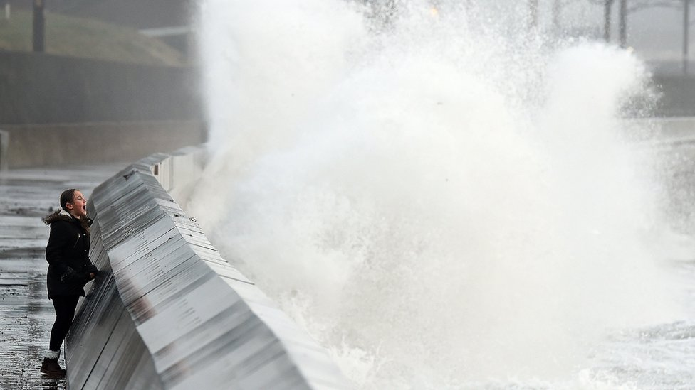 A girl looking as high waves crash into a barrier in a storm