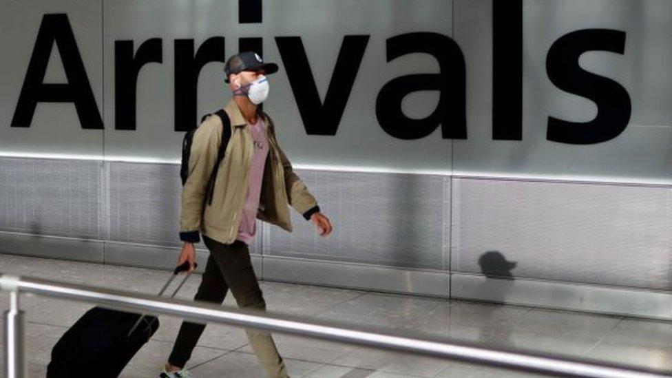 مسافر يرتدي كمامة في صالة وصول بمطار