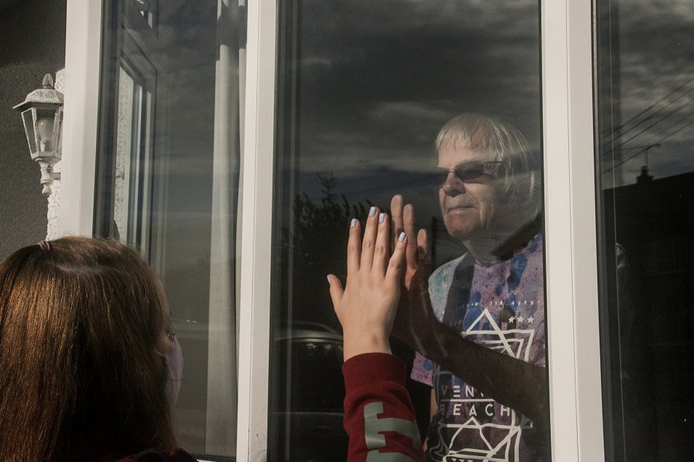 A young person holds their hand up to the window as a relative looks on from the other side
