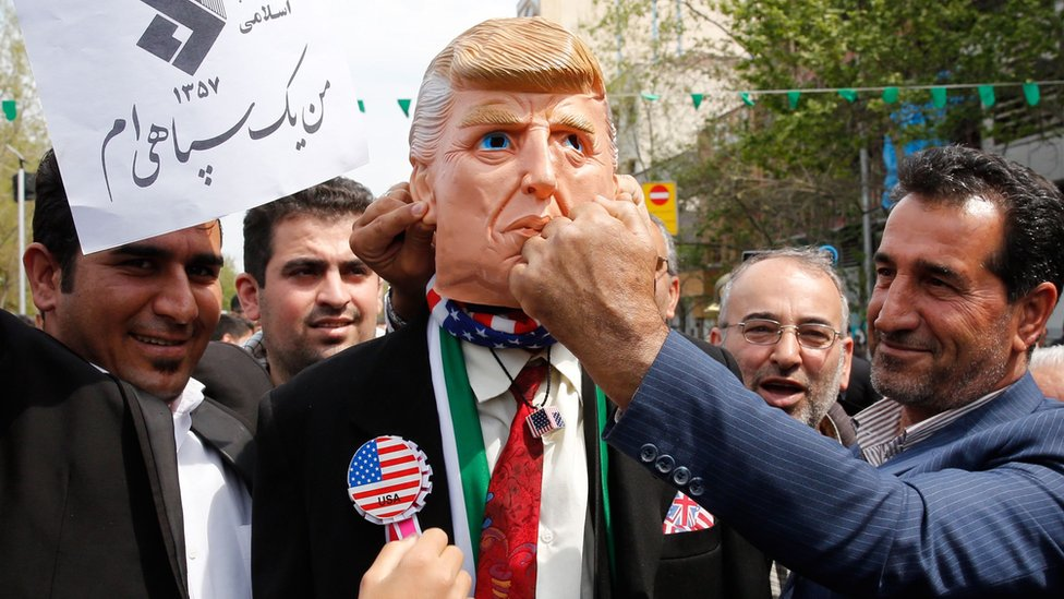 Iranians pretend to hit a man wearing a mask of US President Donald Trump, at a rally in Tehran on 12 April 2019