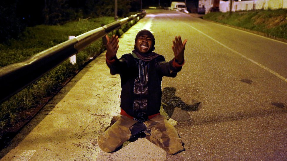 An African migrant celebrates on a road after crossing the border fence between Morocco and Spain's north African enclave of Ceuta, 9 December 2016