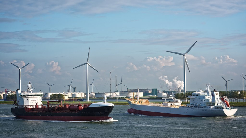 Cargo ships on a canal with wind turbines in the background