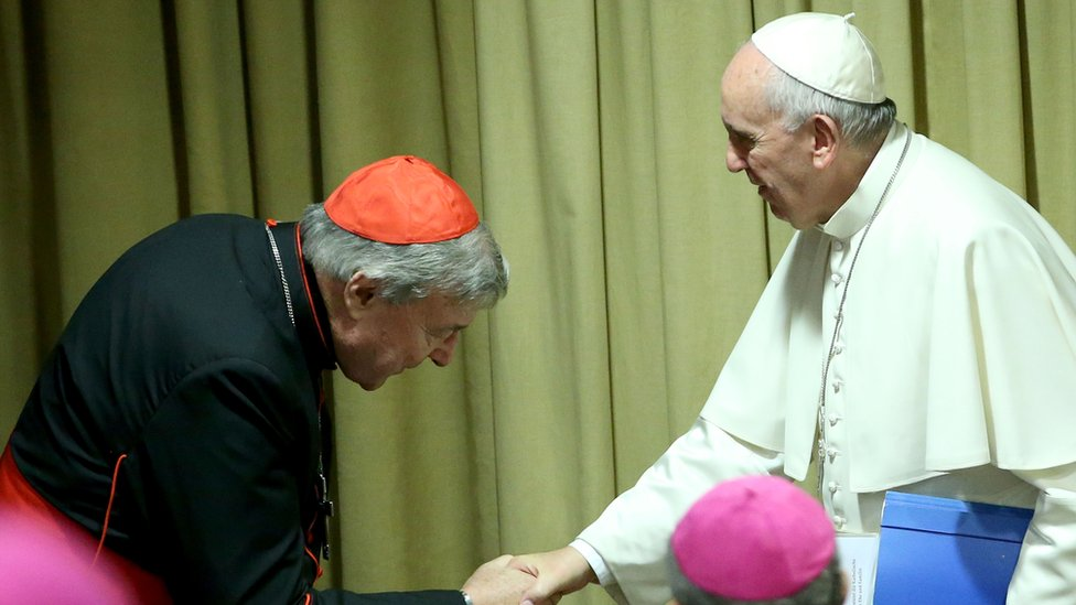 Cardinal Pell, left, bows his head as he sakes the and of Pope Francis in this 2015 photo