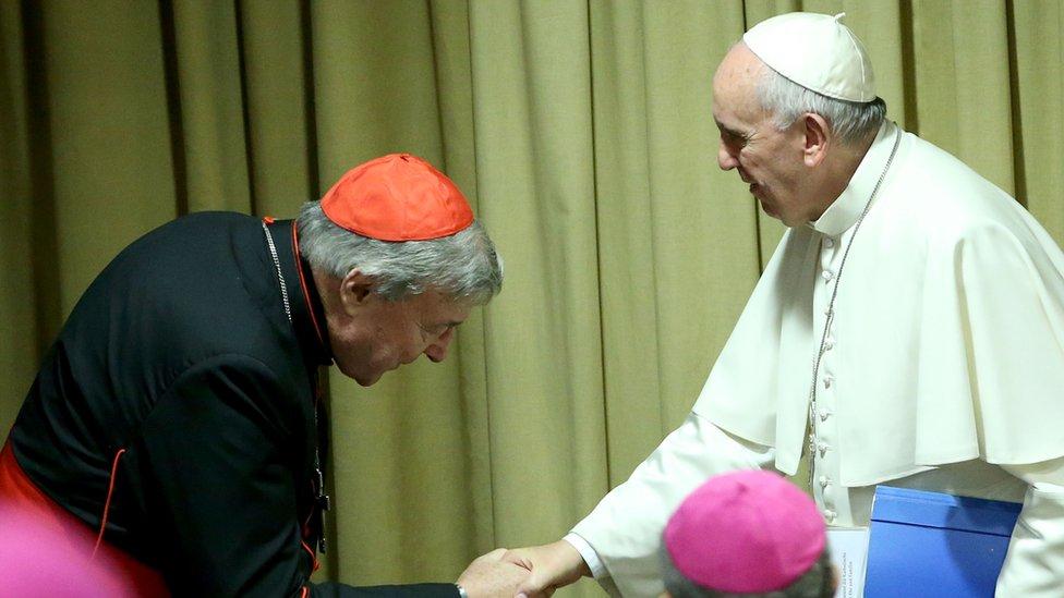 El cardenal Pell (izq.) se inclina para saludar al papa Francisco, en 2015