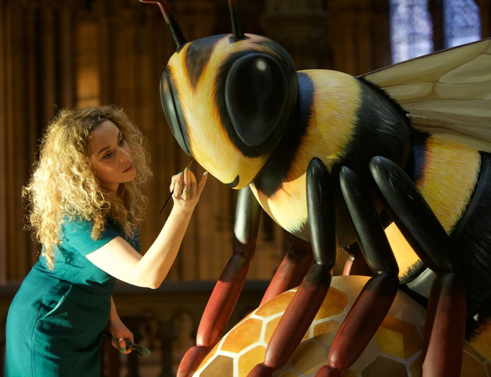 Artist Jodie Silverman puts the finishing touches to one of the bee sculptures
