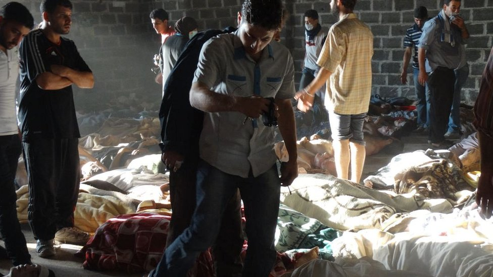 People look at the bodies of people killed in a sarin nerve agent attack in the rebel-held Ghouta region of Damascus on 21 August 2013