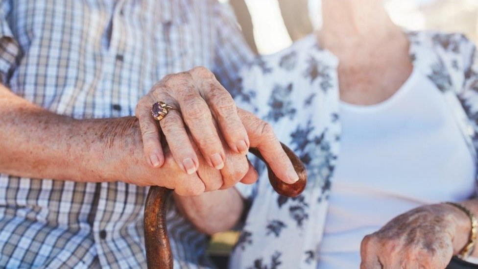 Close up old couple hold hands