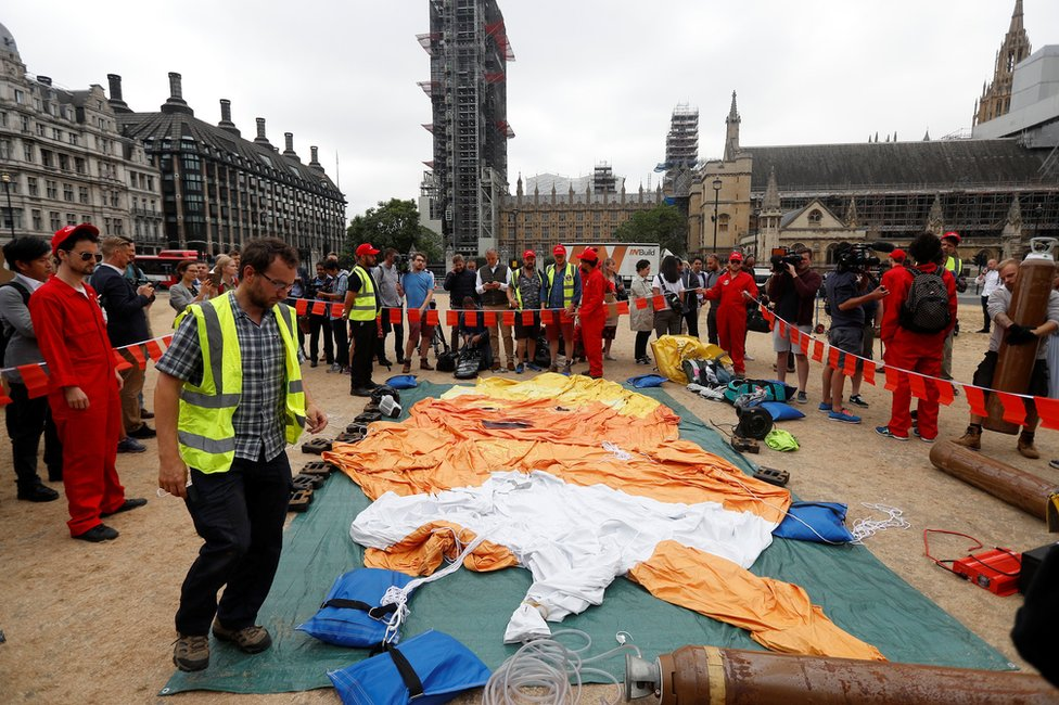 Demonstrators prepare to inflate a blimp portraying US President Donald Trump, in Parliament Square, London