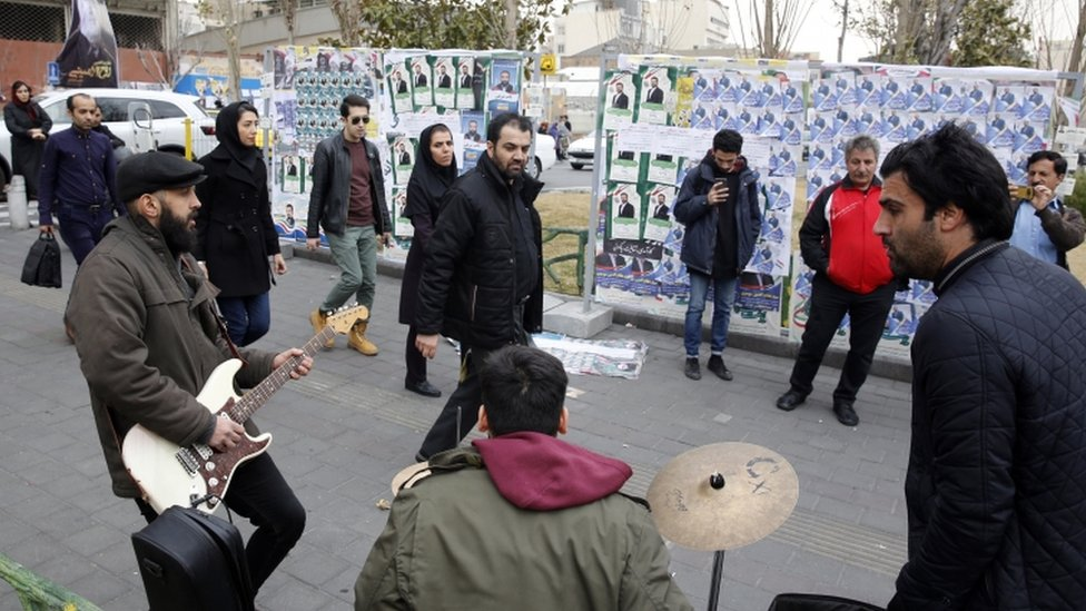 فرقة إيرانية تعزف الموسيقى أمام ملصقات دعائية في العاصمة الإيرانية.