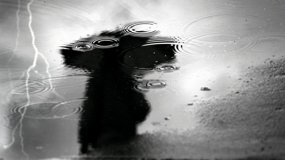 Reflejo de una mujer y rayo en charco de lluvia