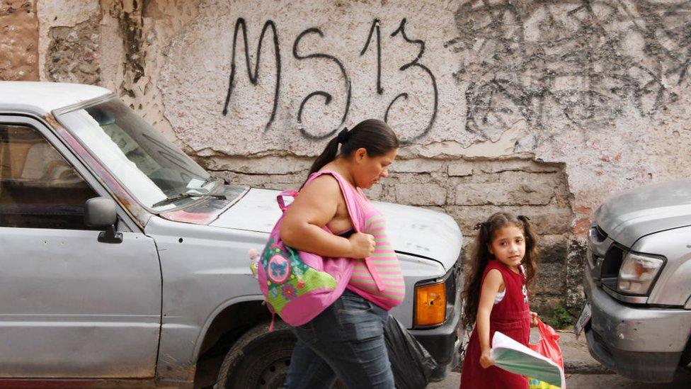 Mujer y niña caminan frente a una pared con la inscripción MS-13