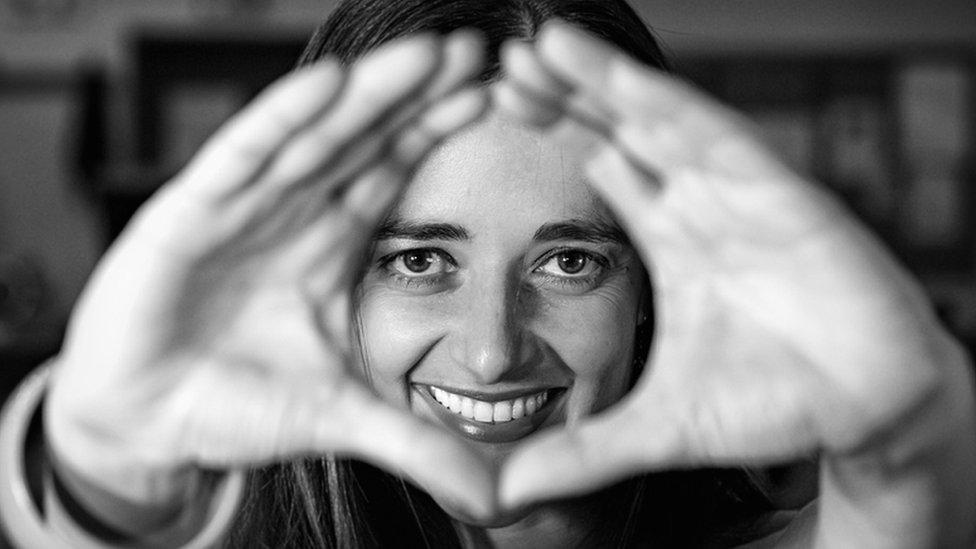 Una mujer hace un gesto de forma redonda con las manos.