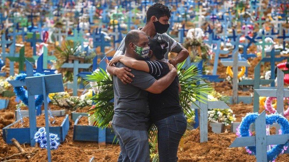 Gente abrazándose en un cementerio