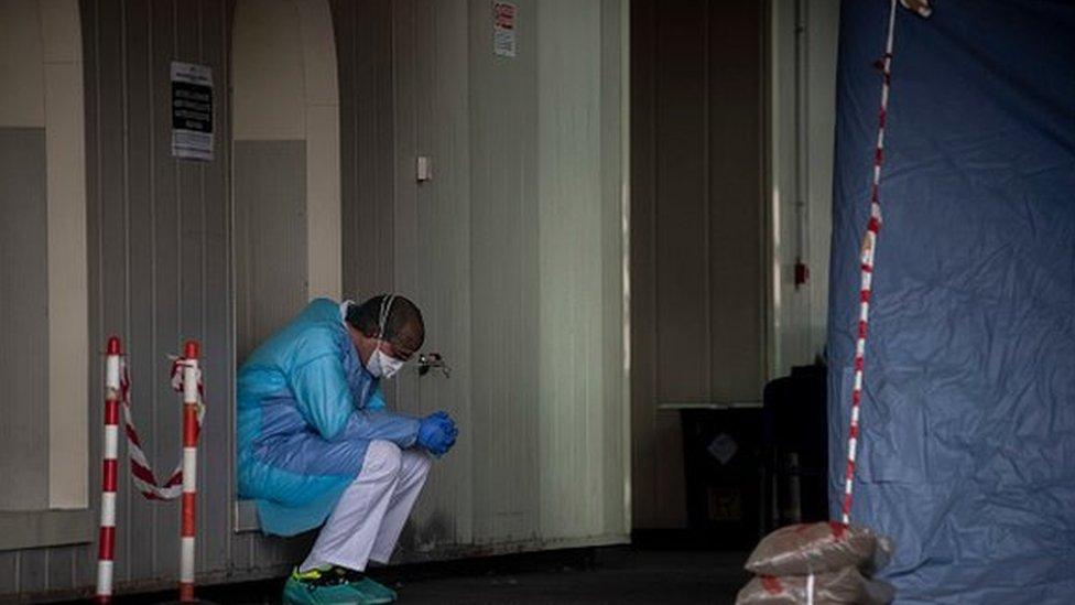 Un trabajador de la salud, sentado con sus manos cruzadas.