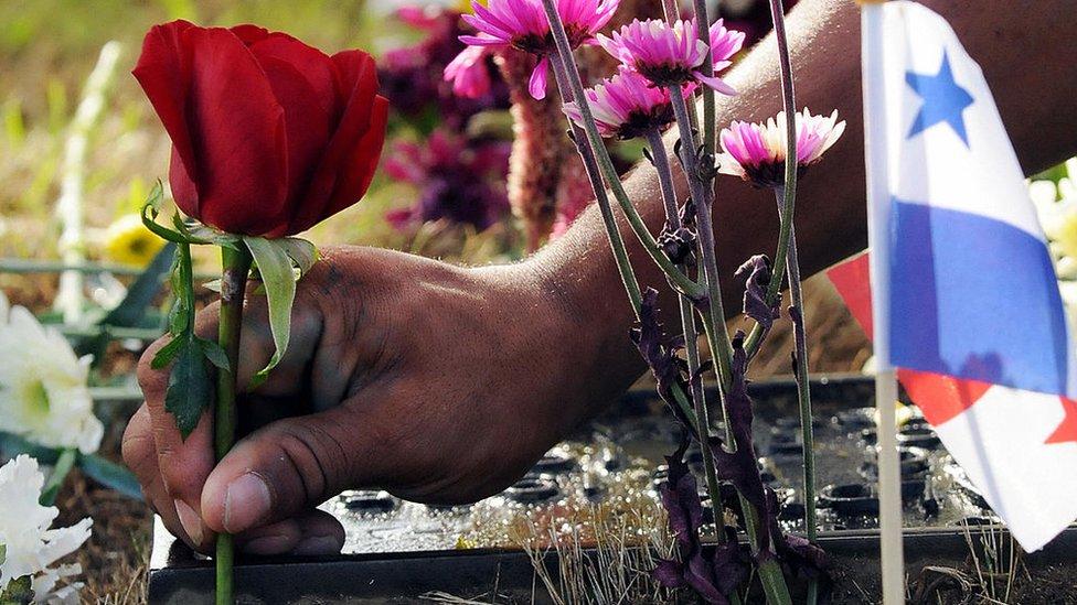 Un niño con una rosa sobre la tumba de un soldado muerto el 20 de diciembre de 1989