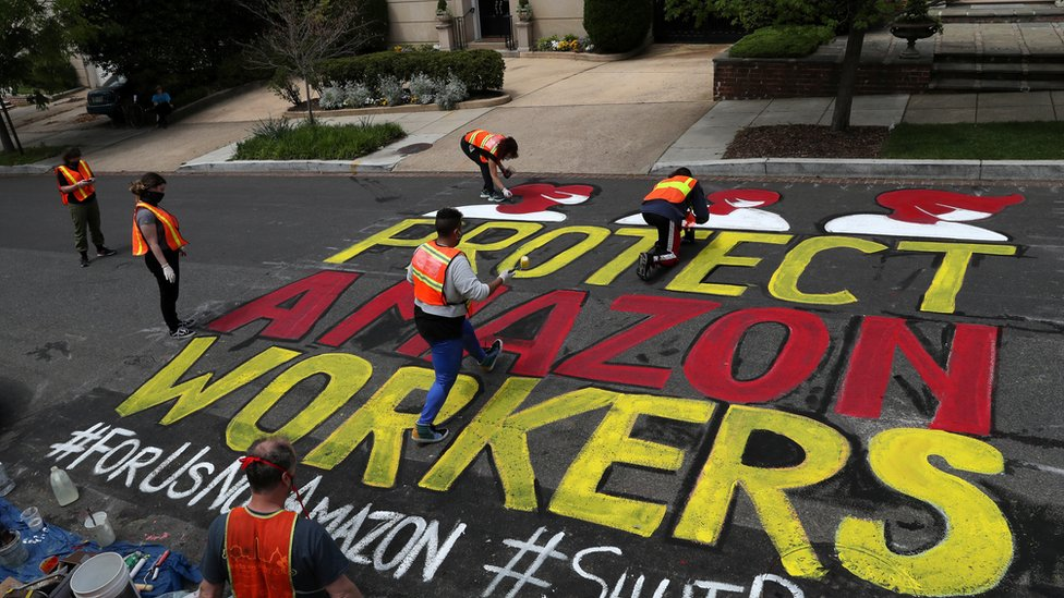 "Several people contribute to paining a very large ""protect Amazon workers"" sign on the road outside a very affluent home"