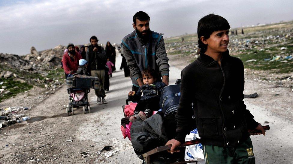 Una familia empuja sus pertenencias en la salida de Mosul.