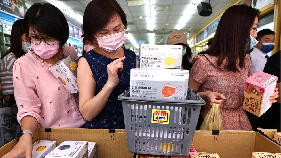 People buy boxes of protective face masks following the outbreak of coronavirus disease (COVID-19), in Taipei, Taiwan, May 12, 2021