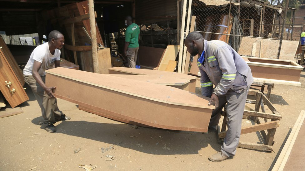 Vincent Nhidza (R) and colleague Mathew Simango (L) arrange coffins at a workshop in Mbare, Harare, Zimbabwe, 18 September
