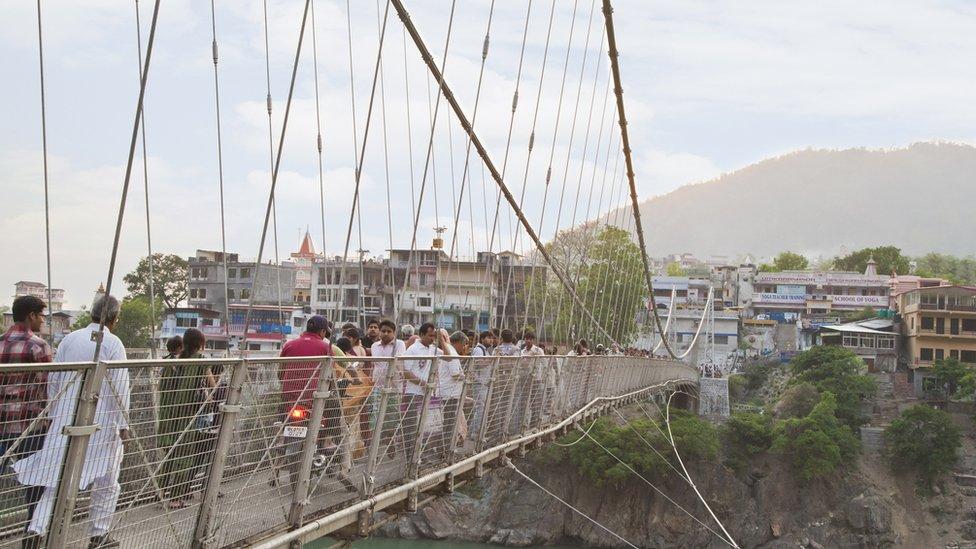 Tourists stand on the Lakshman Jhula suspension bridge