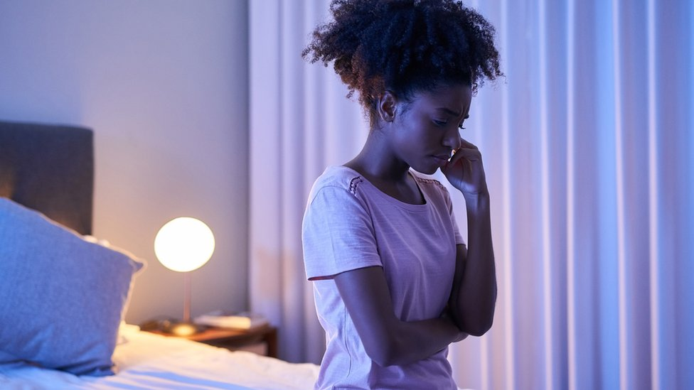 A young woman sitting alone in her bedroom at night.