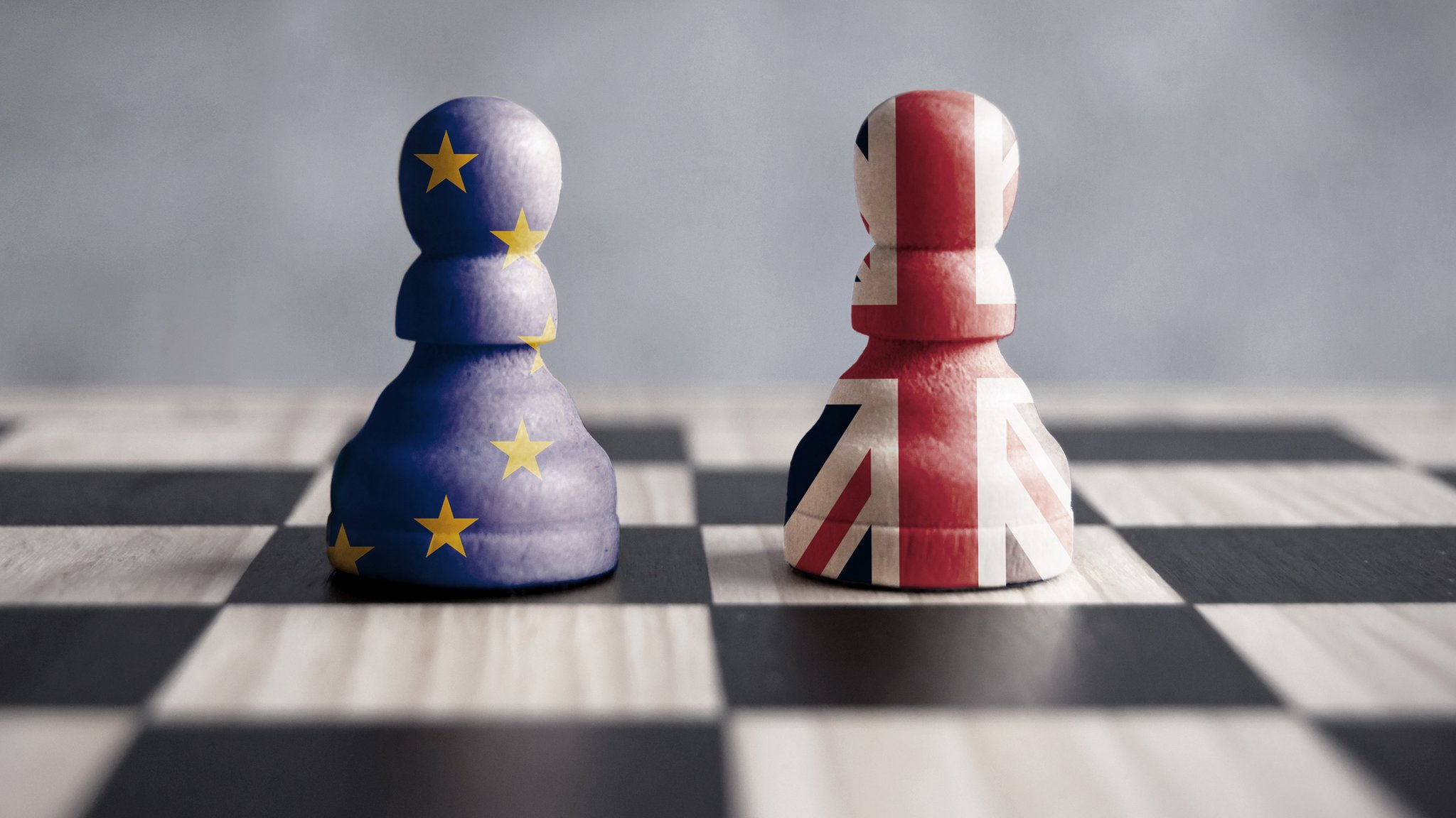 Two chess pieces on a chess board, one enclosed in the EU flag, one enclosed in the union jack.