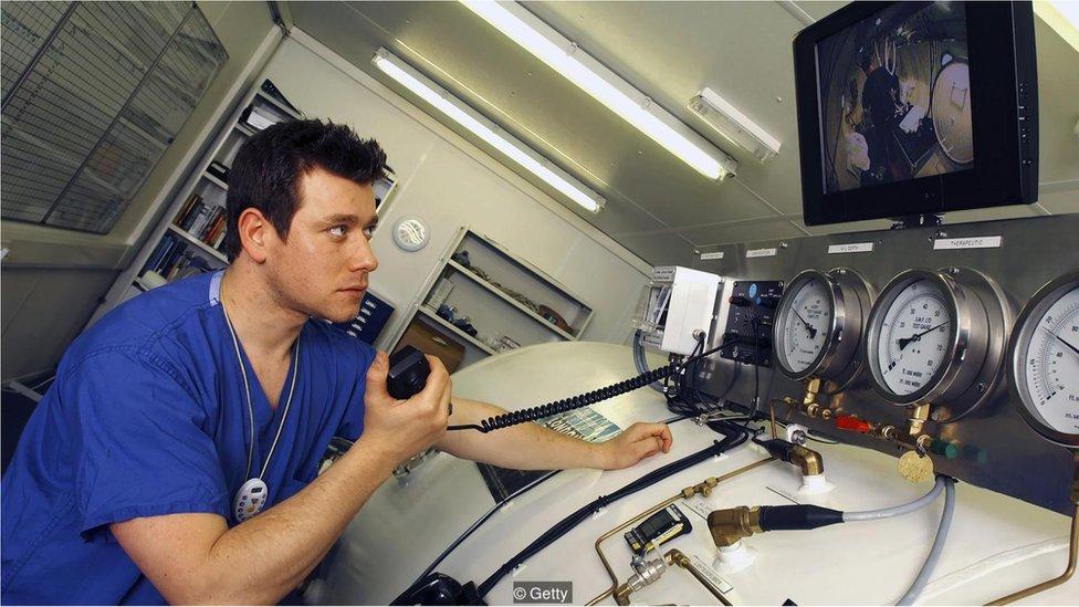 Seorang teknisi berkomunikasi dengan penyelam di ruangan hiperbarik.