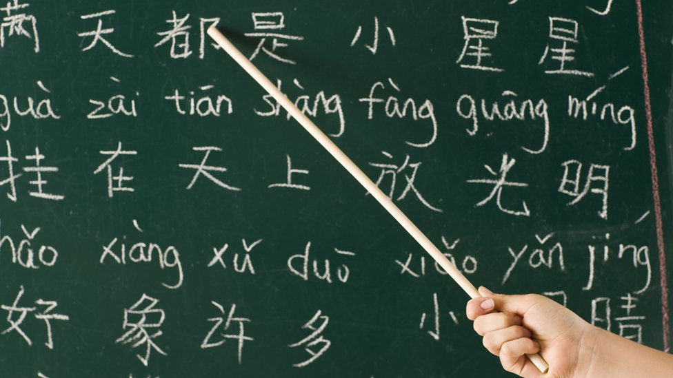 Girl pointing at blackboard in a Chinese lesson
