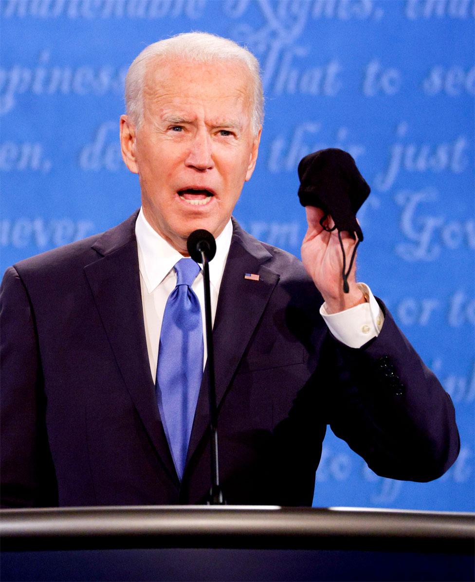 Joe Biden holds up his mask