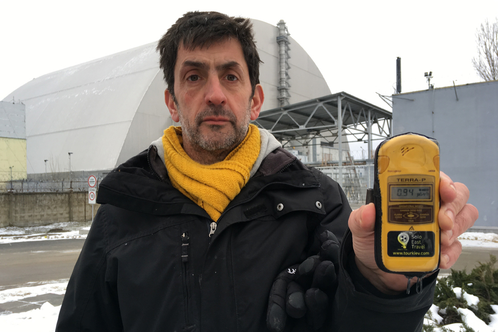 Justin Rowlatt holding a Geiger counter, close to the sarcophagus