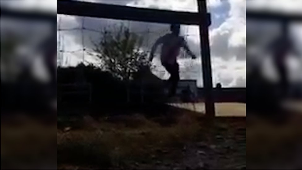 A boy running across the tracks to avoid a train