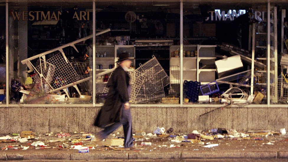 """A picture taken 28 April 2007 shows a man passing by a destroyed shop after two days of riot in the center of Tallinn, after Estonian authorities took measures to remove the """"Monument to the Liberators of Tallinn"""" - an homage"""