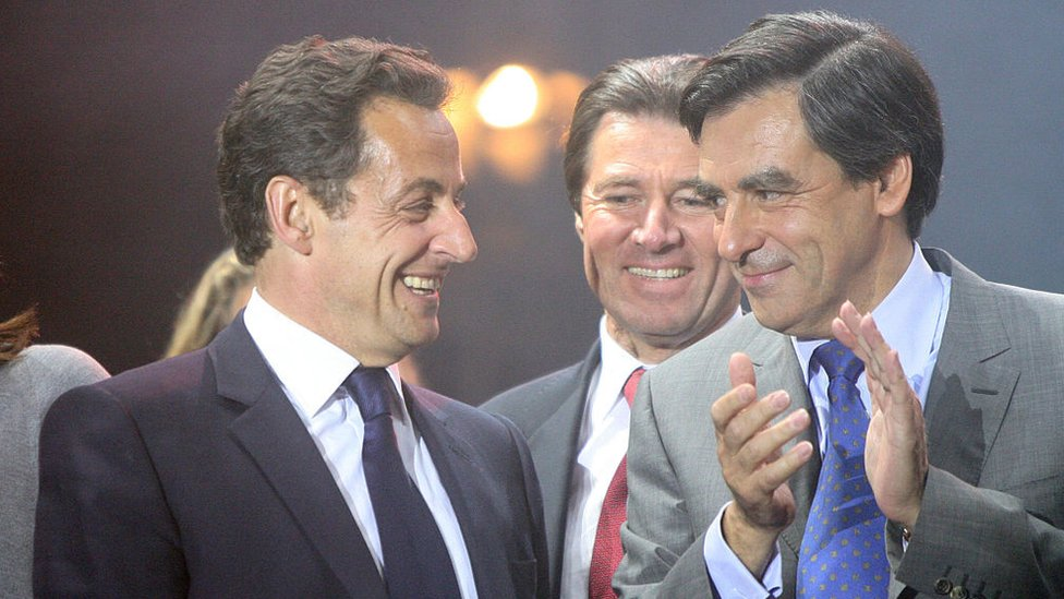 Nicolas Sarkozy, left, laughs on stage alongside Francois Fillon