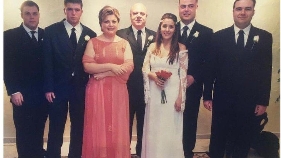 Luiz (no centro) ao lado da esposa, de filhos e de nora posam para foto em casamento. Homens de terno, esposa com vestido rosa e nora está de noiva.