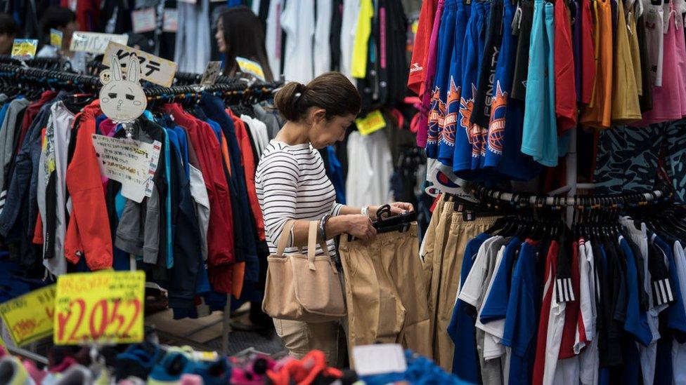 Una mujer japonesa mira ropa.