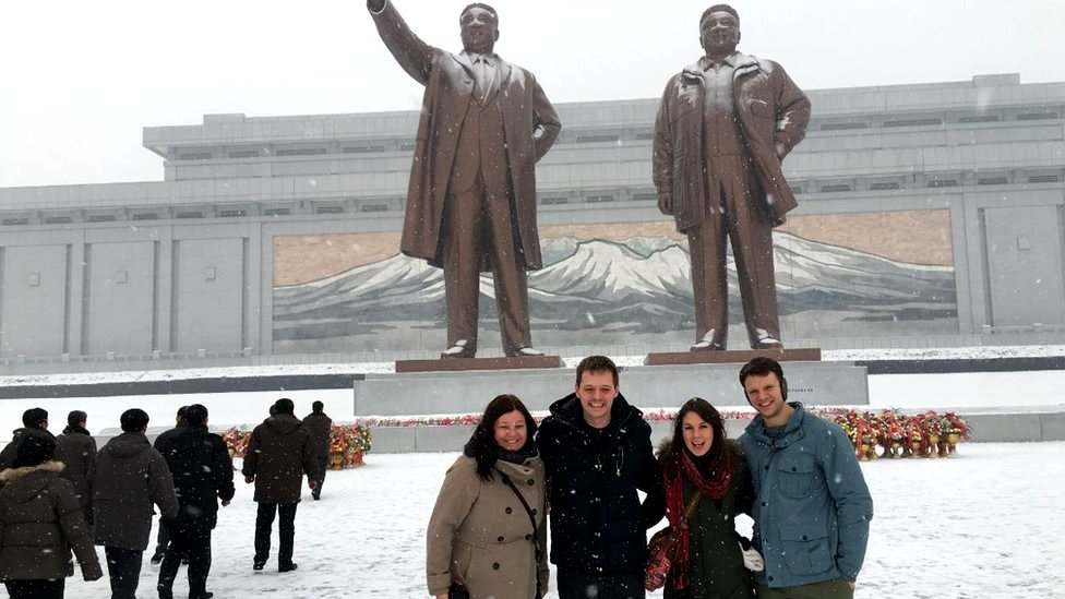 Otto Warmbier and friends pose in front of statues in North Korea