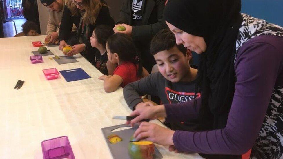 Niños aprenden a picar fruta en un centro comunitario