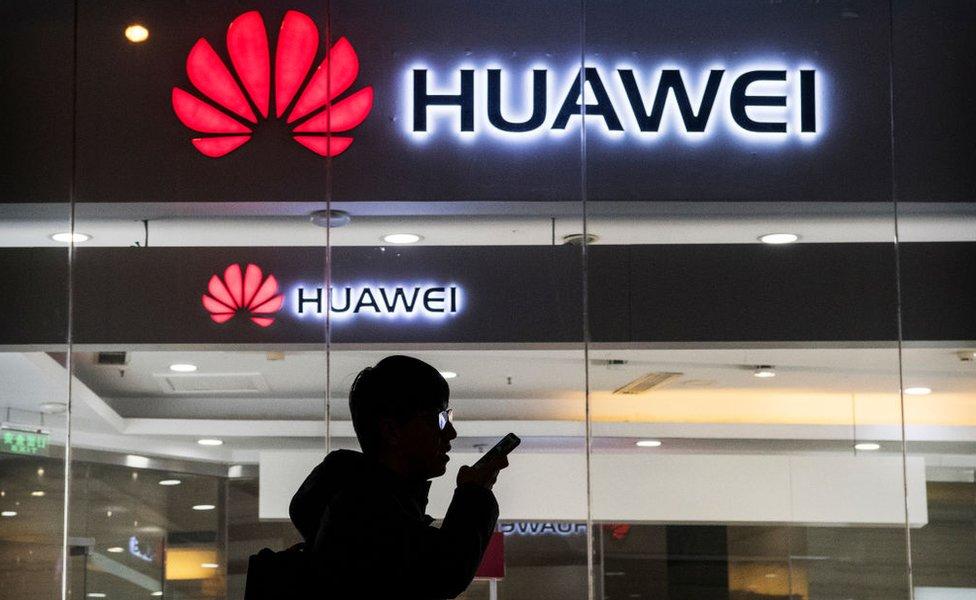 Un ciudadano chino parece hablar por el móvil frente a una tienda de Huawei en Pekín.