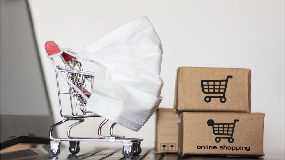 Un carro de la compra y cajas de cartón de compra por internet.