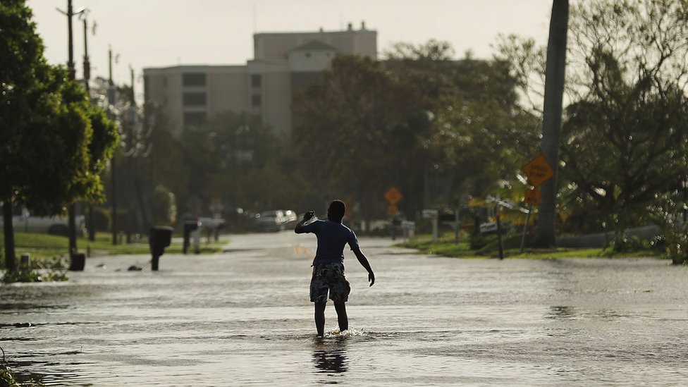 A teen walks through flooded streets the morning after Hurricane Irma swept through the area on September 11, 2017 in Naples, Florida