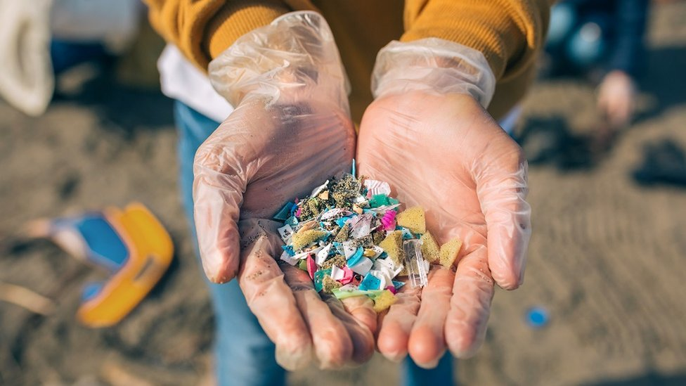 Detail of hands showing multi coloured microplastics on the beach