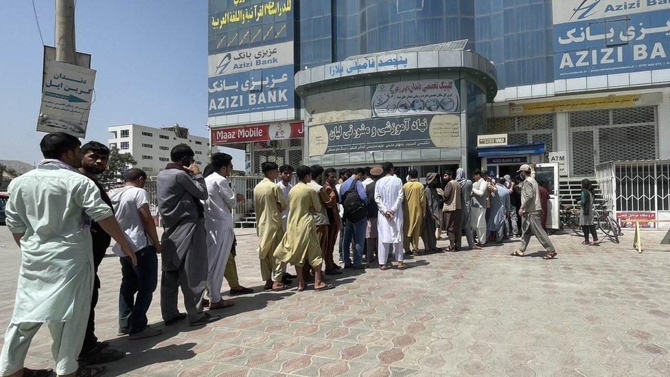 Afaganos fuera de un banco en Kabul
