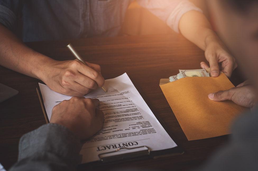 Un hombre firma un contrato a cambio de un sobre de dinero