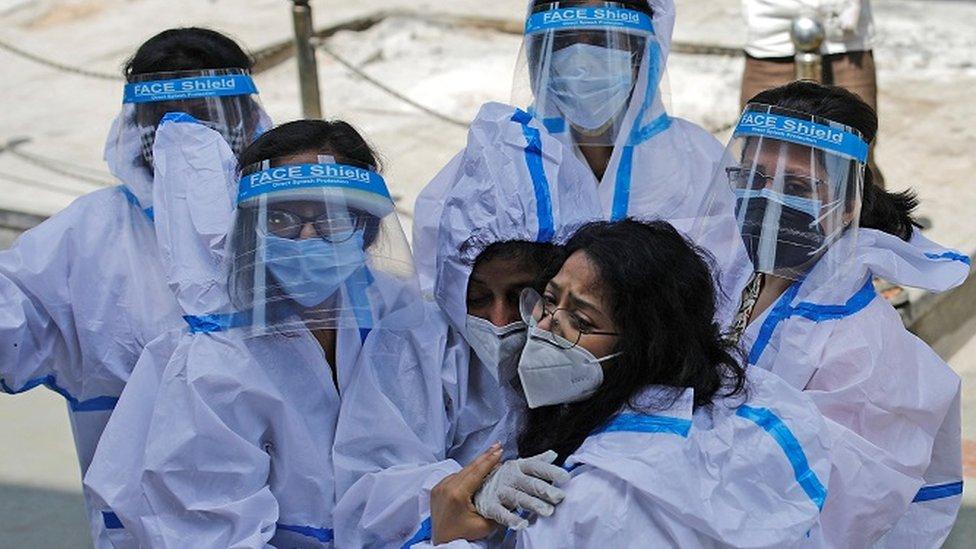 Un grupo de trabajadoras médicas con equipos de protección personal se abrazan