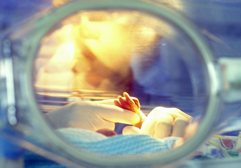 Agarrando la mano de un bebé en incubadora