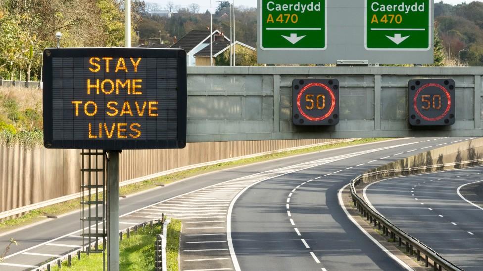 """Carretera vacía rumbo a Cardiff en Gales con un cartel que dice """"Quédate en casa, salva vidas"""""""