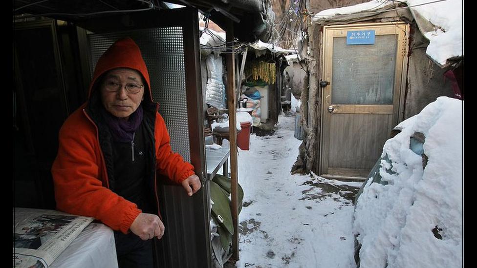 Un hombre mayor surcoreano sentado en el barrio humilde de Guryong de Seúl con nieve en el suelo.