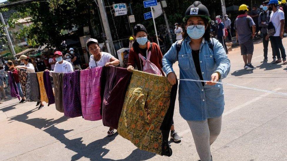 Women create a barrier across a street made of sarongs.