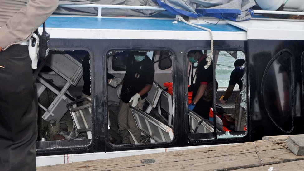 Police investigators examine the Gili Cat 2 boat following an explosion off Bali, Indonesia, on 15 September